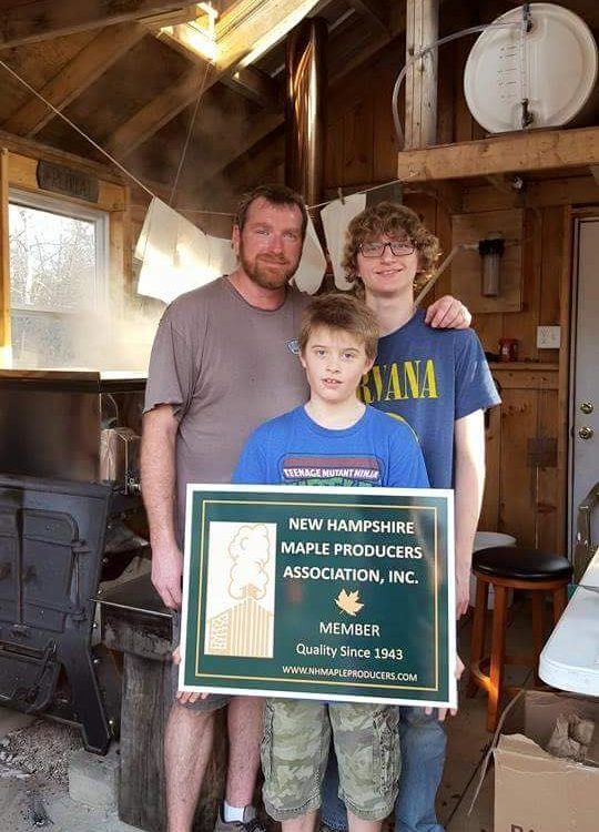 Chris, Zach and Kam White of Tappy Sapmaster and Sons Sugarhouse in Loudon proudly showing their new NHMPA sign